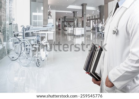 portrait of doctor holding treatise and wheelchair on corridor of hospital - stock photo