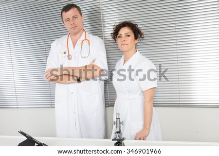 Portrait of doctor in bright surgery with doctor attending patient on grey background - stock photo