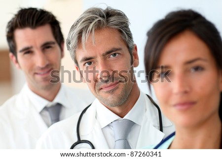 Portrait of doctor standing amongst medical team - stock photo