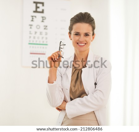 Portrait of doctor woman with eyeglasses in front of snellen chart - stock photo