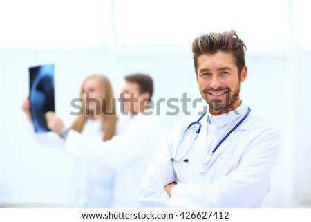 Portrait Of Doctor Working At Nurses Station - stock photo