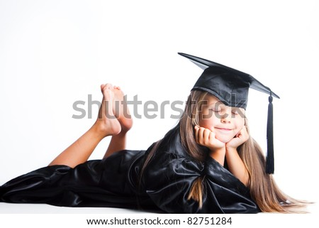 Portrait of dreaming cute girl in black academic cap with liripipe and gown lying on isolated white - stock photo