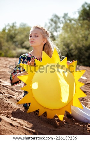 Portrait of dreamy girl posing with paper sun - stock photo