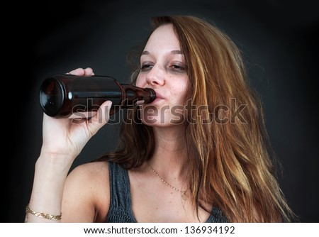 Portrait of drunk young woman drinking beer over black - stock photo