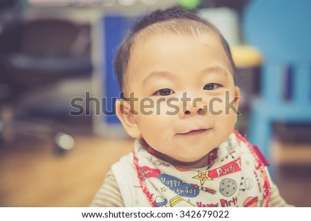 Portrait of eat smeared baby sitting in baby chair - stock photo