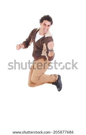 Portrait of ecstatic casual young man jumping in the air with hands raised in fists, Proud man jumping out of joy smiling - stock photo