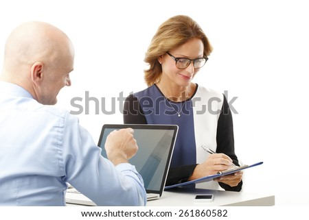 Portrait of efficiency bank employees sitting in front of laptop and digital tablet and analyzing data. Isolated on white background.  - stock photo