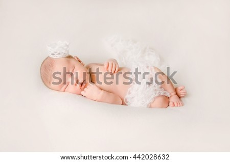 Portrait of eight day old sleeping newborn baby girl with a crown on her head and tender woolen showl