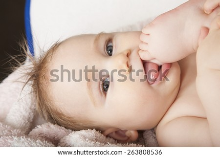 portrait of eight months age blonde lovely cute baby face wet hair licking her foot on mouth lying on towel - stock photo