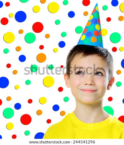 Portrait of eight years boy with birthday cap looking up on white background - stock photo