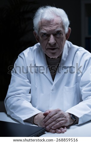 Portrait of elder man in medical apron - stock photo