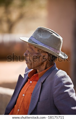 Portrait of elderly  african man with a broken had and old suit - stock photo