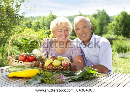Portrait of elderly couple with fresh vegetables on the table - stock photo
