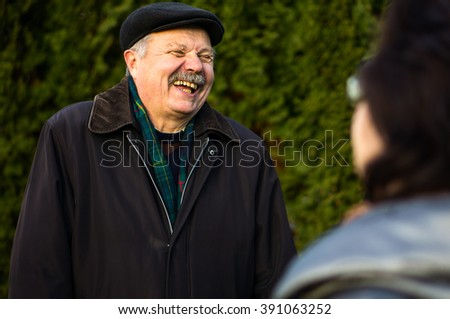 Portrait of elderly man in black hat in wood in autumn - stock photo