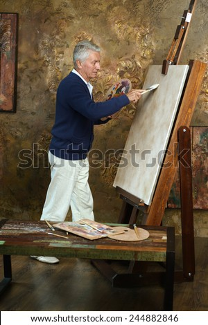 Portrait of elderly man painting with easel - stock photo