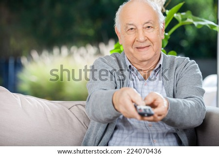 Portrait of elderly man using remote control while sitting on couch at nursing home porch - stock photo