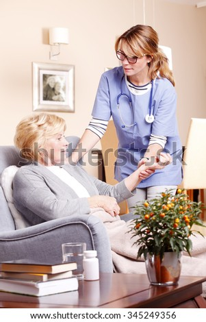 Portrait of elderly patient sitting at home and accepting female nurse helping hand.