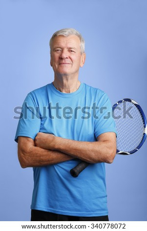 Portrait of elderly retired man holding in his hand a tennis racket while looking at camera and smiling.  Professional coach standing with arms crossed at isolated background.  - stock photo