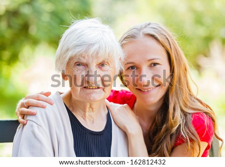 Portrait of elderly woman and her grandchild - stock photo