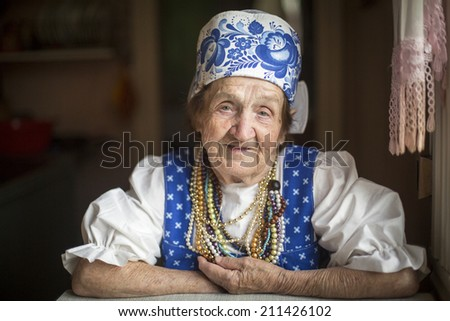 Portrait of elderly woman in ethnic clothes in his house. - stock photo