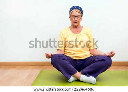 Portrait of Elderly woman practicing yoga in gym. - stock photo