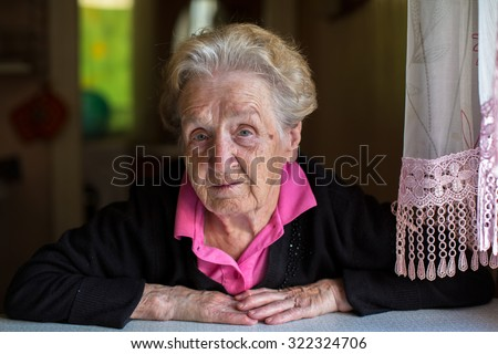 Portrait of elderly woman sitting at the table of the house. - stock photo
