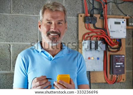 Portrait Of Electrician Standing Next To Fuse Board - stock photo