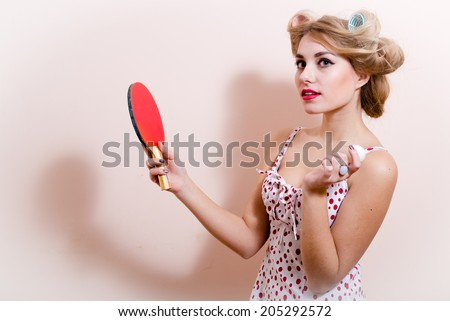 portrait of elegant attractive glamor pinup girl dazedly looking at camera posing in red dress with flower in hair & holding bat ball for table tennis on white or light copy space background closeup - stock photo