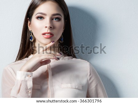 Portrait of elegant beautiful woman in glamour earrings over white background. - stock photo
