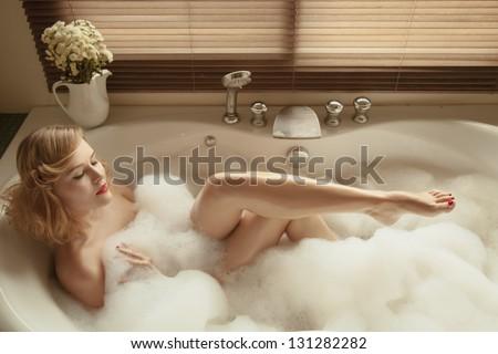 Portrait of elegant beautiful woman relaxing in a spa bath - stock photo