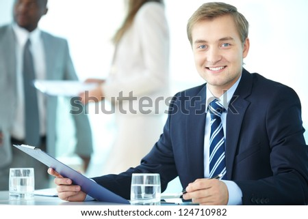 Portrait of elegant boss with clipboard looking at camera