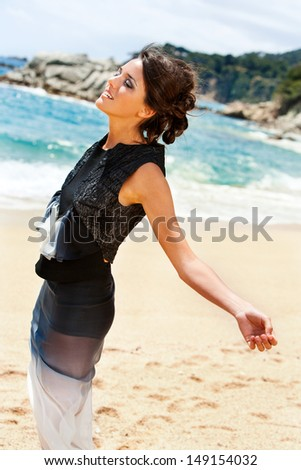 Portrait of elegant brunette in smart dress enjoying sea breeze. - stock photo