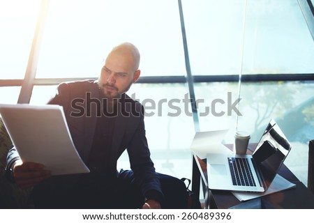 Portrait of elegant business man looking over some paperwork sitting next to big window in office interior, male executive studies documents or papers during his coffee time, flare sun light - stock photo