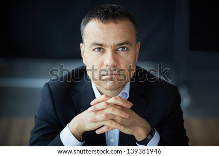 Portrait of elegant businessman looking at camera - stock photo