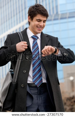 Portrait of elegant businessman looking at his watch with office building behind - stock photo
