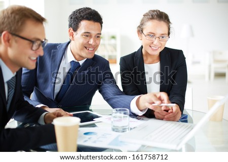 Portrait of elegant businessman pointing at laptop screen while explaining something to his colleagues at meeting