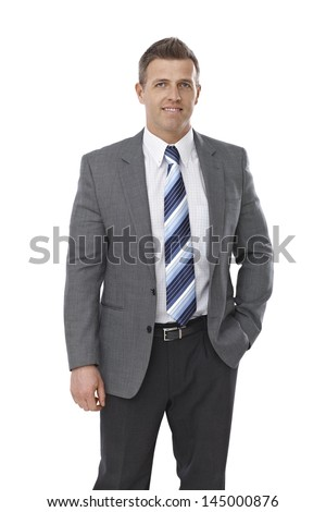 Portrait of elegant businessman standing with hands in pockets over white background. - stock photo