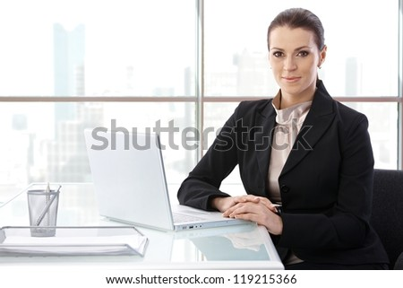 Portrait of elegant businesswoman sitting at desk with laptop computer, smiling at camera, copyspace. - stock photo