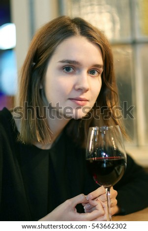 Portrait of elegant charming young glamour woman in restaurant with glass of red wine/Closeup portrait of a pretty girl with a glass