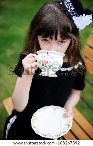 Portrait of elegant child girl in a black dress having a tea party outdoors, focus on a tea cup - stock photo