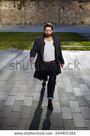 Portrait of elegant fashionable adult man dressed in coat walking in urban setting, stylish hipster man walking on the street at sunny evening - stock photo
