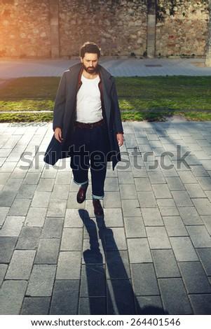 Portrait of elegant fashionable adult man dressed in coat walking in urban setting, stylish hipster man walking on the street at sunny evening, flare sunshine - stock photo
