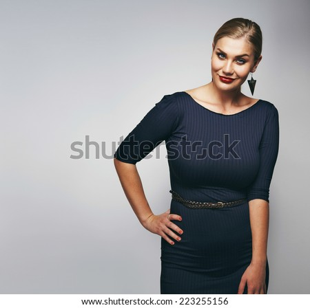 Portrait of elegant female model standing with her hand on hip against grey background.  - stock photo