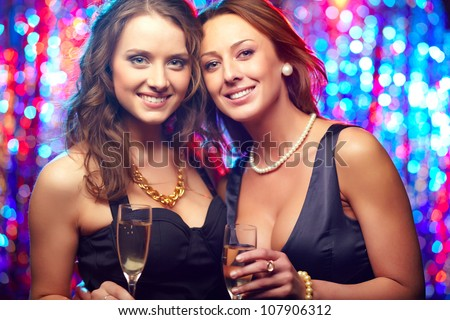 Portrait of elegant girlfriends partying holding flutes of champagne
