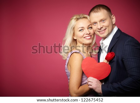 Portrait of elegant happy couple with red paper heart looking at camera