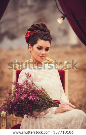 portrait of elegant lady sitting on a chair with a bouquet of flowers.  Fashion beautiful sensual brunette woman with makeup - stock photo