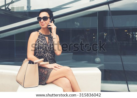 Portrait of elegant lady talk on mobile phone while relaxing after walking on the street in summer day, confidence female business woman calling with smart phone while sitting outdoors in summer day - stock photo