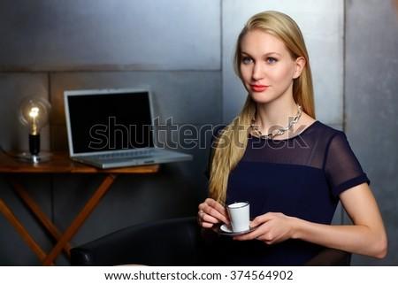 Portrait of elegant nordic type businesswoman having coffee-break, looking away. - stock photo
