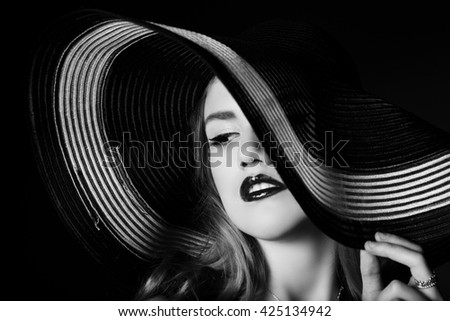 Portrait of elegant woman in black and white hat. Studio shot - stock photo
