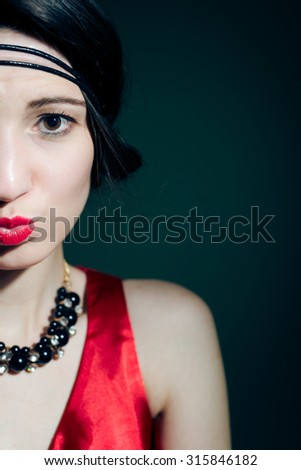 Portrait of elegant woman in retro accessories with red lips. Closeup of beautiful girl in 1920s styled red costume on dark blurred background. - stock photo